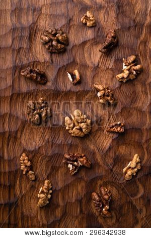 Walnut kernels scattered across the carved wooden board. Healthy nuts and seeds composition, background.