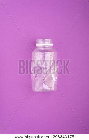 Squashed plastic bottle on vivid purple background. Plastic utilisation concept. Ecological problem, global environment.