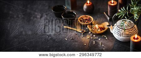 Tea Time on Dark Shale Background. White Iron Asian Teapot With Burning Candles