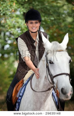 young horsewoman with white horse