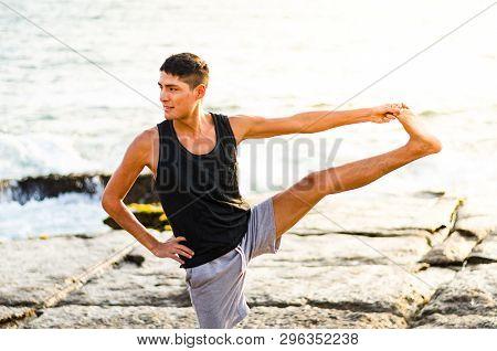 Young Man Practicing Yoga, Doing Parivrtta Utthita Hasta Padangusthasana Exercise, Twisting Extended