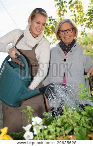 grandmother and lovely blonde watering plants outdoors