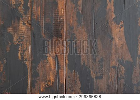 The old wooden surface background, scuffed boards with black paint stains.