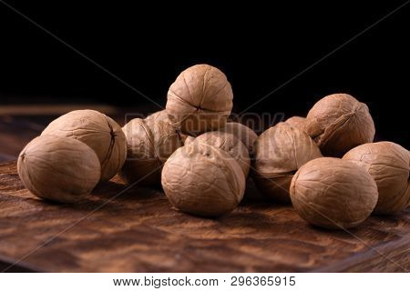 Bunch of walnuts on carved wooden board, dark background. Healthy nuts and seeds composition, background.