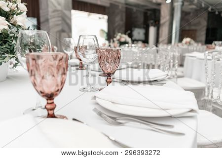 Wine Glasses On Round Banquet Table Served. Interior Of Restaurant For Wedding Dinner, Ready For Gue