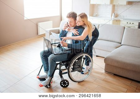 Student With Disability Sitting On Wheelchair. Cheerful Woman Stand Behind And Embrace Him. Looking