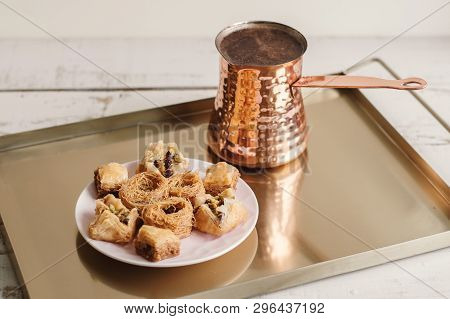 Plate With Assorted Baklava And Turkish Coffe In A Cezve Served On A Metal Gold Colored Metal Tray
