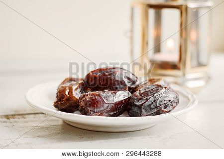 Plate With Dried Dates And Lantern With Candle On Wooden Table. Traditional Sweet Food During Holy M