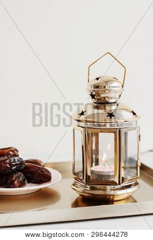 Golden Lantern With Small Candle And Dried Dates On Metal Tray. Ramadan Celebration