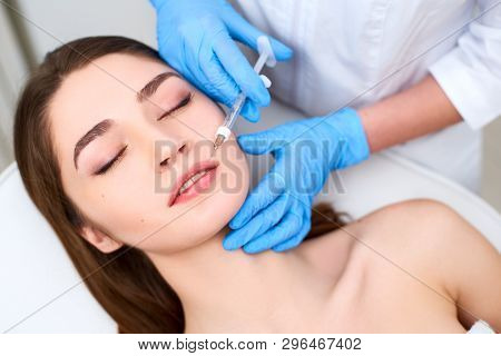 Lip Augmentation. Closeup Of Beautician Doctor Hands Doing Beauty Procedure To Female Lips With Syri
