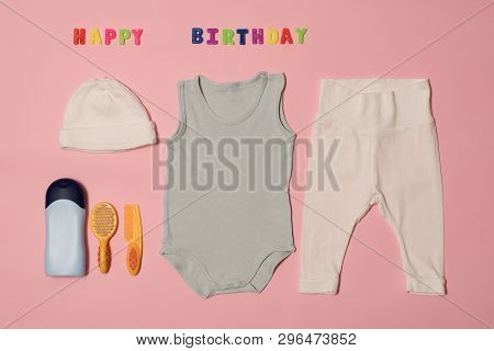 Set Of Clothes And Accessories For Newborn. Colored Inscription Happy Birthday On A Pink Background.