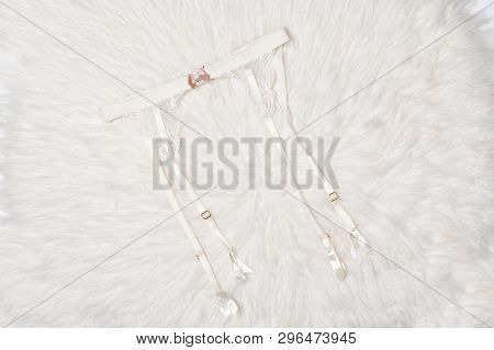 White Lace Suspenders For Stockings On A White Fur. Close-up. Fashion Lingerie Concept