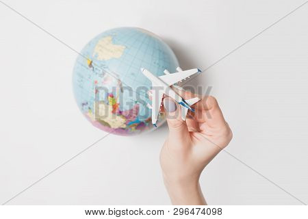 Passenger Plane In A Female Hand On The Background Of The Globe. Flight Concept On A Light Backgroun