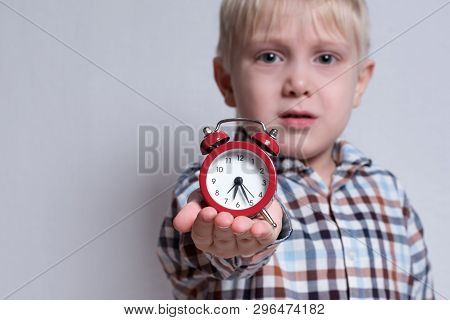 Little Blond Boy With A Red Alarm Clock In His Hands. Morning Concept. Light Background