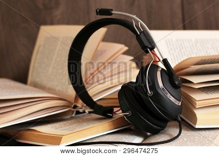 Audio Book Concept. Headphones And Old Book Over Wooden Table. Music.