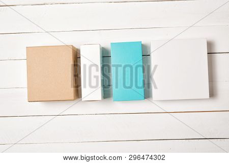 Multicolored Gift Boxes On A Light Wooden Background. Flat Lay.