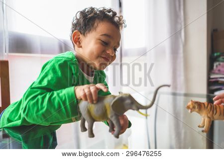 Latin American Kid Playing With Animal Toys At Home . Mixed Race Kid Playing On A Glass Table Indoor