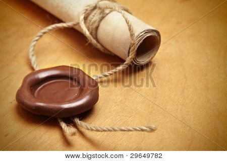 Scroll with wax seal on a wooden table poster