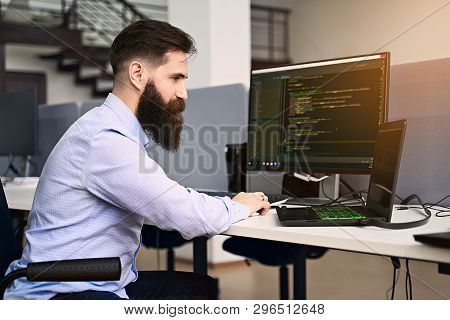 Software Programming. Bearded Man Working On Computer In It Office, Sitting At Desk Writing Code, Wo