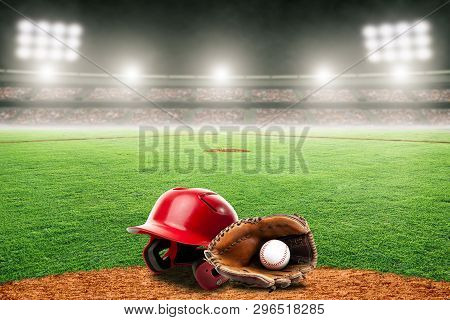 Baseball Helmet, Glove And Ball On Field At Brightly Lit Outdoor Stadium. Focus On Foreground And Sh