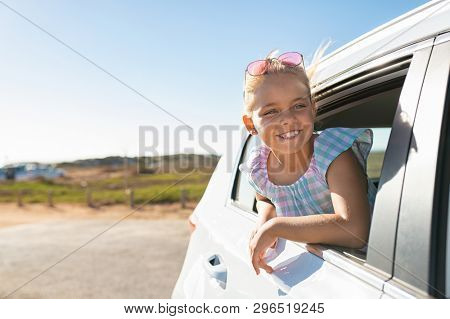 Cute blonde girl in the car looking through window. Smiling little girl having fun travelling by car and looking out. Happy smiling child sticking her head out of window and looking road trip.