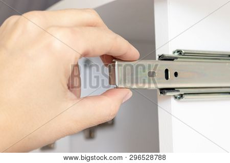 Assembling furniture from chipboard, hand holding roller guide of a drawer on white plank poster