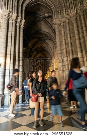 PARIS, FRANCE, SEPTEMBER 1, 2018 : Asian tourist woman posing in the Notre Dame de Paris cathedral