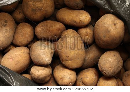 Overflowing bag of potatos close-up for background poster