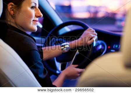 Driving a car at night - pretty, young woman driving her modern car at night in a city (shallow DOF; color toned image)