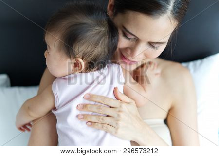 Crop Shot Of Beautiful Asian Mother Holding Baby's Back On The Bed. Seen From Behind The Baby. Mothe
