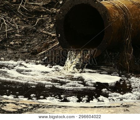 Dirty Water Flows Out Of The Old Rusty Pipe Without Cleaning. Pollution Of Natural Water Bodies