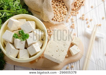 Soy Bean Curd Tofu In Clay Bowl And In Hemp Sack On White Wooden Kitchen Table. Non-dairy Alternativ