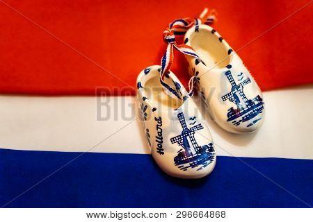 Mini Ceramic Souvenir Clogs From Holland On Dutch Flag Background