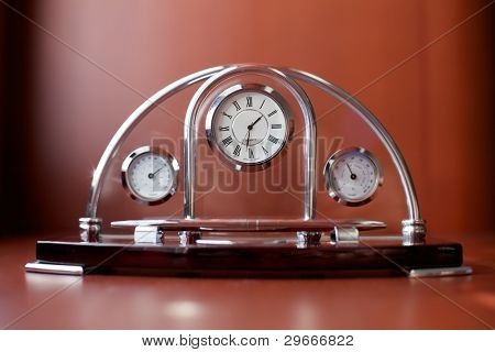 Souvenir clock, thermometer and barometer on a brown table.