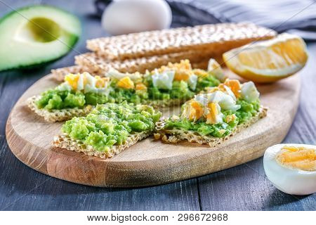 Rye, Wheat Crisp Bread With Avocado And Egg On Wooden Background. Crisp And Avocado Sandwich.