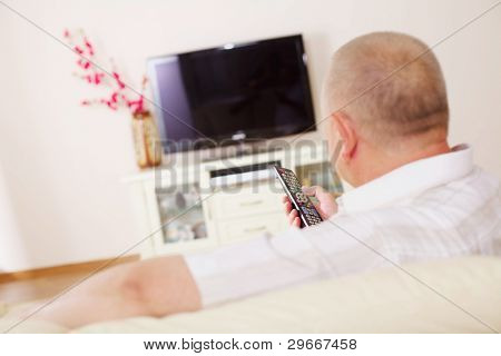 Middle aged man in home bright living room sitting on comfortable couch and watching TV