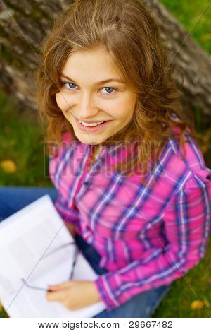 Beautiful smiling student holding book sitting under tree in summer park outdoor