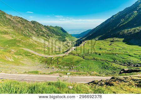 Transfagarasan Road Though Mountains. Wonderful Sunny Forenoon Weather. Rocky Slopes And Grassy Hill