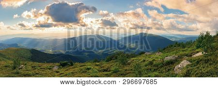 Panorama Of A Gorgeous Summer Sunset In Mountains. Sun Behind The Fluffy Clouds. Rocks Among Grassy