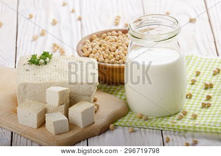Non-dairy Alternatives Soy Milk Or Yogurt In Mason Jar And Tofu On White Wooden Table With Soybeans