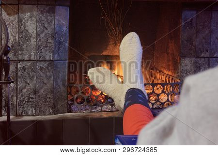 Feet In Woollen Socks By The Fireplace. A Man Rests Near The Fireplace And Warms His Legs In Wool So