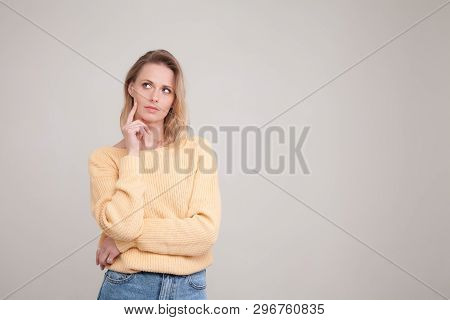 Waist-up Portrait Of Blonde Woman With Puzzled Face Expression , Keeps Her Finger On Cheek, Looks As