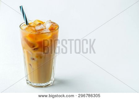 Ice Coffee In A Tall Glass With Cream Poured Over And Coffee Beans. Cold Summer Drink On A Light Bac