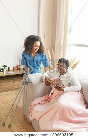 Caring Nurse Coming To The Woman Lying And Reading The Book