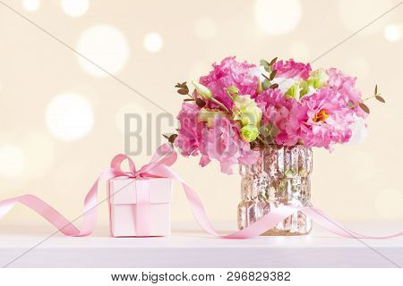 Gift Or Present Box And Beautiful Flowers Bouquet In Vase On Pastel Bokeh Background. Greeting Card