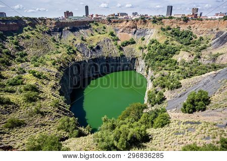 Kimberley, South Africa, 10th April -2019: View Of Open Pit Mine With Lake. City In Background.
