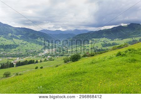 Mountain Village In Valley With Pastures And Fenced Hayfields On Slope On A Foreground Against Storm