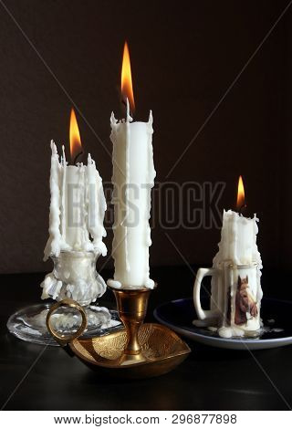 Still Life With Three Vintage Candlesticks With Burning Candles Against Low Key Background. Selectiv