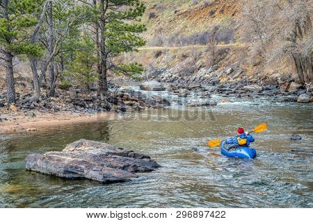 paddler in an inflatable packraft on a mountain river in early spring - Poudre River above Fort Collins, Colorado