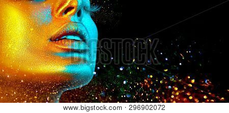 Fashion model woman skin face in bright sparkles, colorful neon lights, beautiful sexy girl lips, mouth. Trendy glowing gold skin make-up. Art design make up. Glitter metallic shine makeup